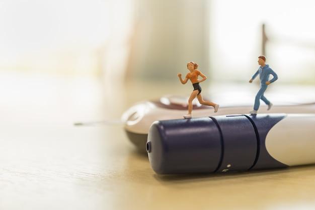 Medizin, diabetes, glykämie, gesundheitswesen und leutekonzept - nah oben von der frauen- und mannläuferminiaturzahl, die auf lanzette mit glukosemeter auf holztisch läuft.