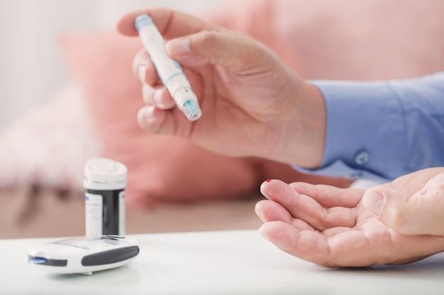 Medizin, diabetes, glykämie, gesundheitswesen und personenkonzept - nahaufnahme des männlichen fingers mit teststreifen