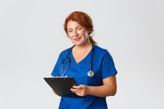 Medizin-, gesundheits- und coronavirus-konzept. freundlich aussehende süße ärztin, ärztin in peelings, die die zwischenablage hält und den patienten ansieht, fragen stellt, die gesundheit überwacht, die untersuchung durchführt.