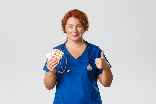 Medizin-, gesundheits- und coronavirus-konzept. zuversichtlich lächelnde ärztin, arzt zeigt daumen hoch als ratschlag behandlung von grippe, influenza oder allergie, zeigt tabletten, empfehlen pillen.