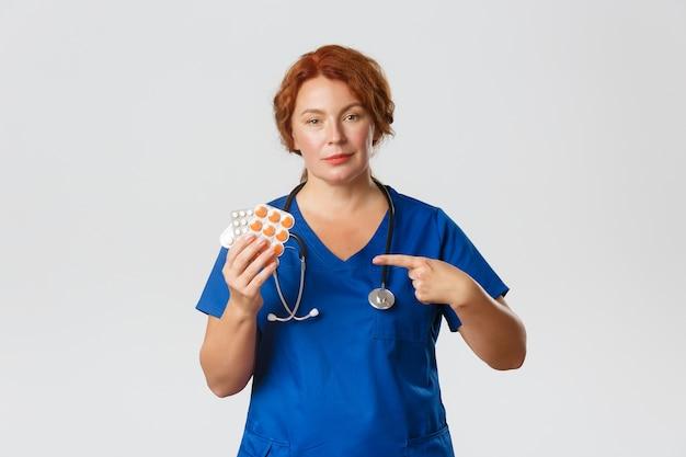 Medizin-, gesundheits- und coronavirus-konzept. zuversichtlich professionelle medizinische mitarbeiterin, ärztin in peelings verschreiben behandlung, zeigefinger auf tabletten, pillen oder vitamine, grauer hintergrund.