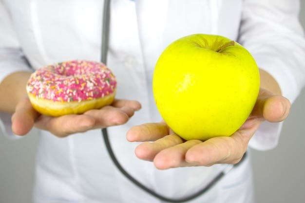 Medizin, gesundheitskonzept. nahaufnahme der hände der ärztin mit einem apfel und einem donut. gesunde ernährung. das konzept des diätvergleichs.