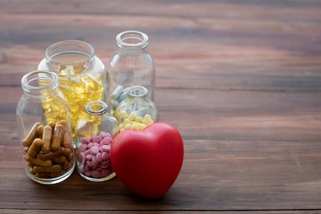 Medizin in der flasche und im herzen auf hölzerner tabelle.