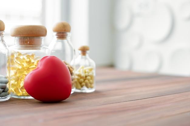 Medizin in der glasflasche und im herzen auf hölzerner tabelle.