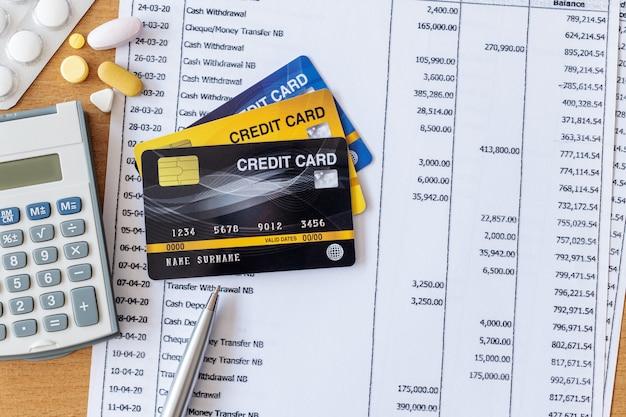 Medizin und taschenrechner auf kontoauszug und kreditkarte auf einem holztisch