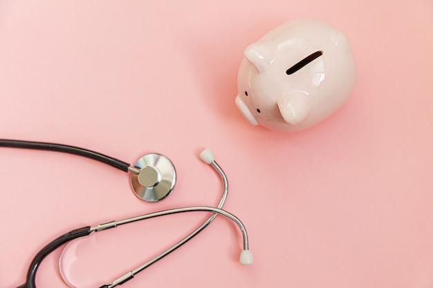 Medizinarztausrüstung stethoskop und sparschwein lokalisiert auf rosa pastellhintergrund. finanzielle überprüfung des gesundheitswesens oder einsparung für das konzept der krankenversicherungskosten.