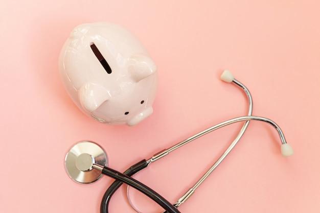 Medizinarztausrüstung stethoskop und sparschwein lokalisiert auf rosa pastellwand. finanzielle überprüfung des gesundheitswesens oder einsparung für das konzept der krankenversicherungskosten. kopierraum für flache draufsicht.