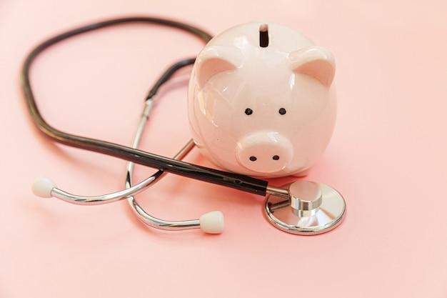Medizinarztausrüstung stethoskop und sparschwein lokalisiert auf rosa pastellwand. finanzielle überprüfung des gesundheitswesens oder einsparung für das konzept der krankenversicherungskosten. speicherplatz kopieren.