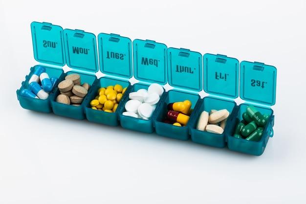 Medizinbehälterkonzept im kleinen glas lokalisiert auf weißem hintergrund