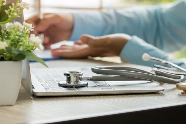 Medizindoktorhand, die für patienten an beratungsraum, arbeitend an laptop-computer auf schreibtisch in der klinik erklärt