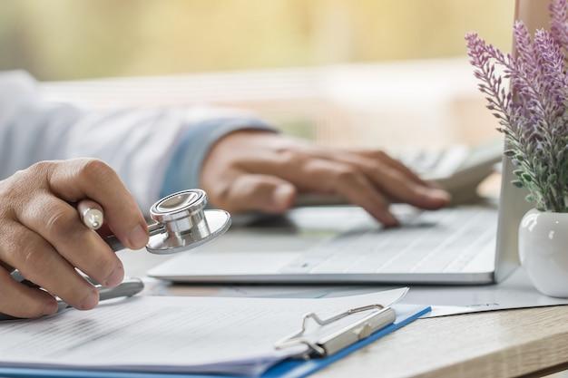 Medizindoktorhand, die stethoskope am beratungsraum, arbeitend an laptop-computer auf schreibtisch in der klinik hält