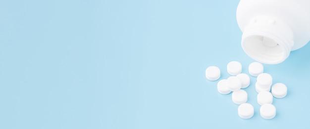 Medizindosen und weiße pillen auf blauem hintergrund isoliert. medizinisches konzept.
