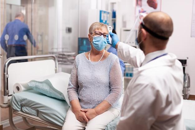 Mediziner, der ein digitales thermometer verwendet, um die temperatur eines älteren patienten mit gesichtsmaske während des coronavirus zu überprüfen