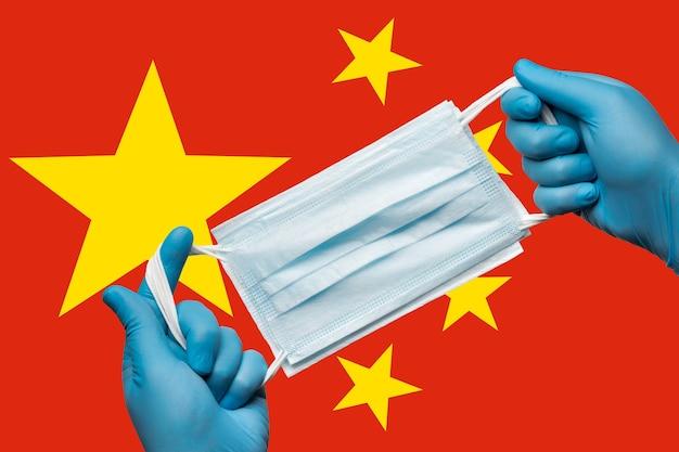 Mediziner, der eine atemschutzmaske in blauen handschuhen auf der hintergrundflagge der volksrepublik china in den händen hält. konzept coronavirus quarantäne, grippe, pandemieausbruch. medizinischer verband für das gesicht.