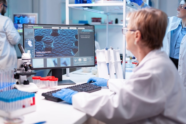 Mediziner, der einen test in einen computer für krankenhausgutachten analysiert