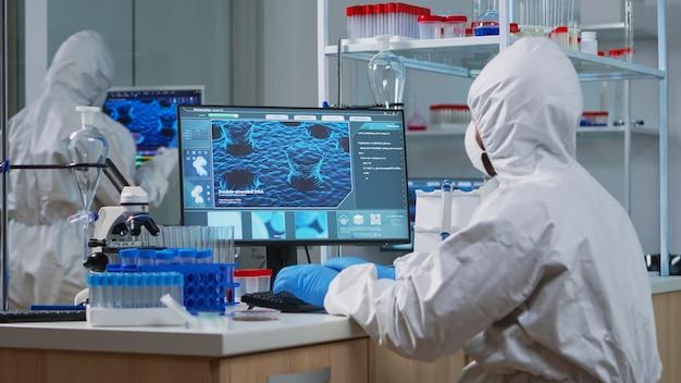 Mediziner im ppe-anzug, der mit dna-scan-bildeingabe auf dem pc in einem ausgestatteten labor arbeitet. untersuchung der impfstoffentwicklung mit hightech- und chemiewerkzeugen für die wissenschaftliche forschung zur virusentwicklung