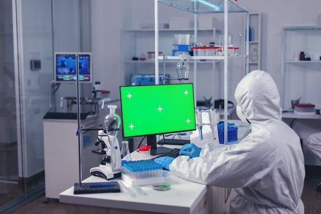 Mediziningenieur, der während des covornavirus an einem computer mit grünem bildschirm forscht