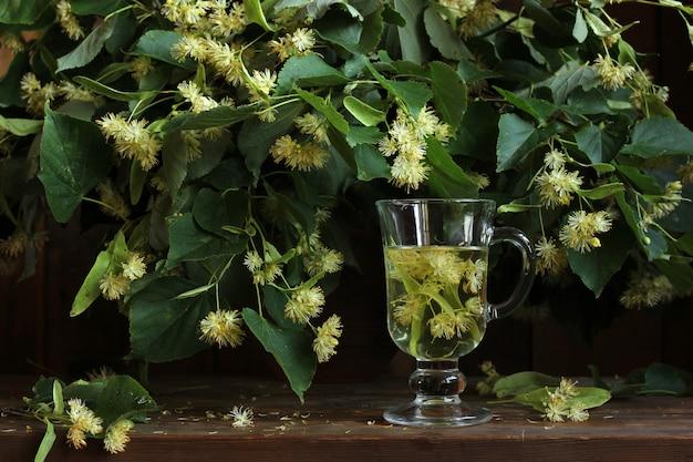 Medizinisch das abkochen von lindenblüten im glas. blühende zweige einer linde. ein volksheilmittel gegen erkältungen.
