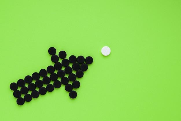 Medizinische aktivkohle in form eines pfeils, der auf eine weiße pille auf einem grünen hintergrund zeigt.