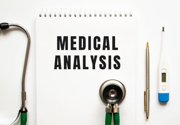 Medizinische analyse text geschrieben in einem notizbuch, das auf einem schreibtisch und einem stethoskop liegt. medizinisches konzept.