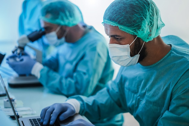 Medizinische arbeiter im hazmat-anzug arbeiten mit laptop und mikoroskop im laborkrankenhaus während des ausbruchs des coronavirus