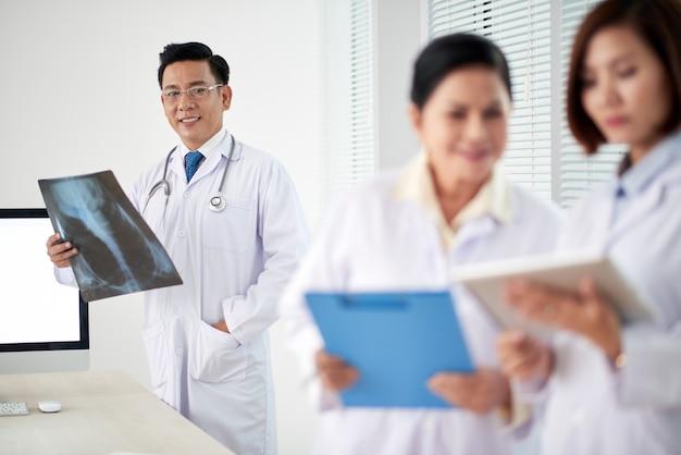 Medizinische arbeitskräfte, die ein concilium, männlichen doktor mit röntgenstrahl im fokus haben