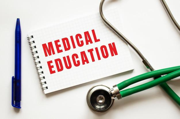 Medizinische ausbildung geschrieben in einem notizbuch auf einem weißen tisch neben stift und stethoskop