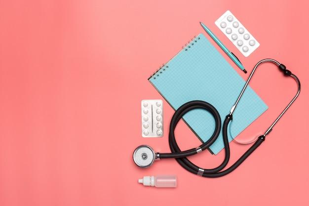 Medizinische ausrüstung auf einem rosa pastellhintergrund mit copyspace.