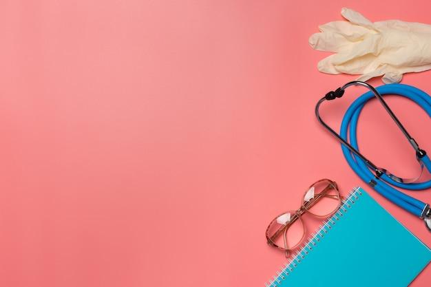 Medizinische ausrüstung auf einem rosa pastellhintergrund.