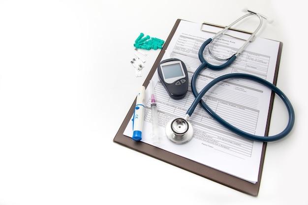 Medizinische ausrüstung auf weißem hintergrund. gesundheits- und medizinisches hintergrundkonzept. blutuntersuchungsgeräte für diabetes und blutzuckermessgerät