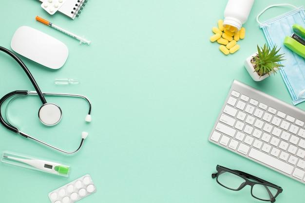 Medizinische ausrüstung und laptop mit saftiger anlage auf grünem pastellhintergrund