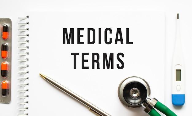 Medizinische begriffe stehen in einem notizbuch auf einem weißen tisch neben pillen und einem stethoskop. medizinisches konzept