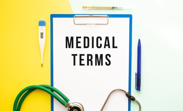 Medizinische begriffe text auf einem briefkopf in einem medizinischen ordner auf einem schönen hintergrund. stethoskop, thermometer und stift.