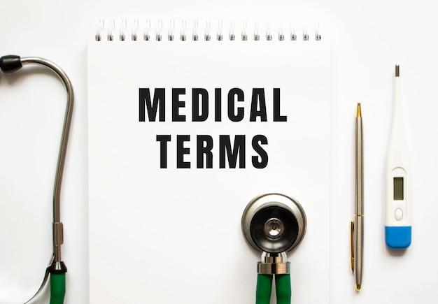 Medizinische begriffe text geschrieben in einem notizbuch, das auf einem schreibtisch und einem stethoskop liegt