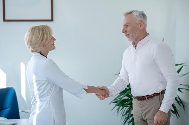 Medizinische beratung. grauhaariger männlicher patient, der dem blonden ärztin die hand schüttelt