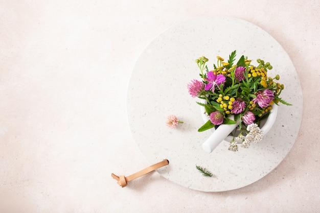 Medizinische blumen kräuter im mörser. alternative medizin. klee schafgarbe rainfarn rosebay
