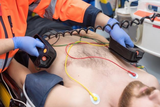 Medizinische dringlichkeit im krankenwagen. notarzt, der defibrillator verwendet