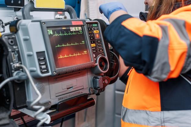 Medizinische dringlichkeit im krankenwagen. notarzt mit defibrillator.