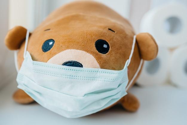 Medizinische einweg-gesichtsschutzmaske auf braunem teddybär