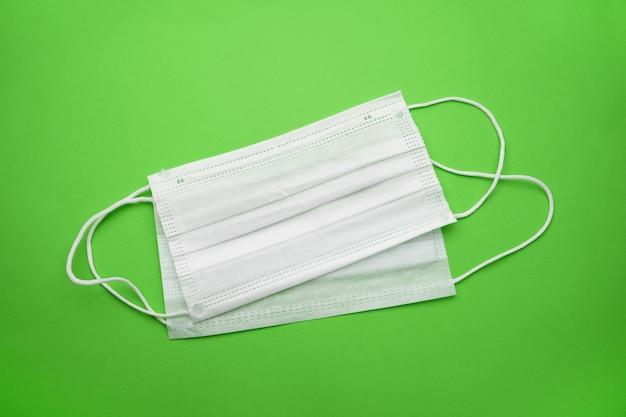 Medizinische einweggesichtsmasken isoliert auf einer grünen wand