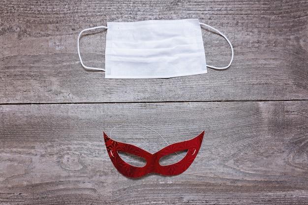 Medizinische einwegmaske im vergleich zu masquarade-gesichtsmaske in der mitte der roten weihnachtsmütze