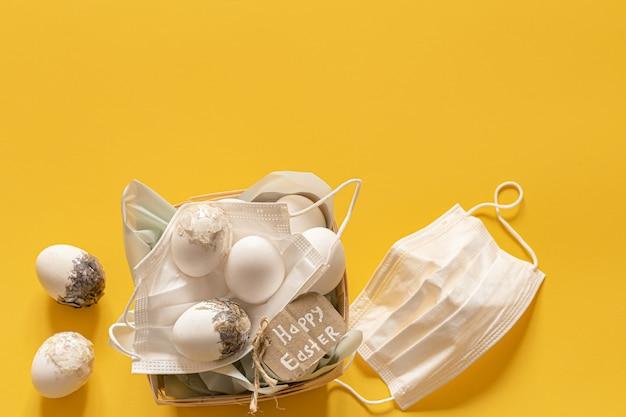 Medizinische einwegschutzmasken und dekorative eier. ungewöhnliche ostern während der coronavirus-pandemie.