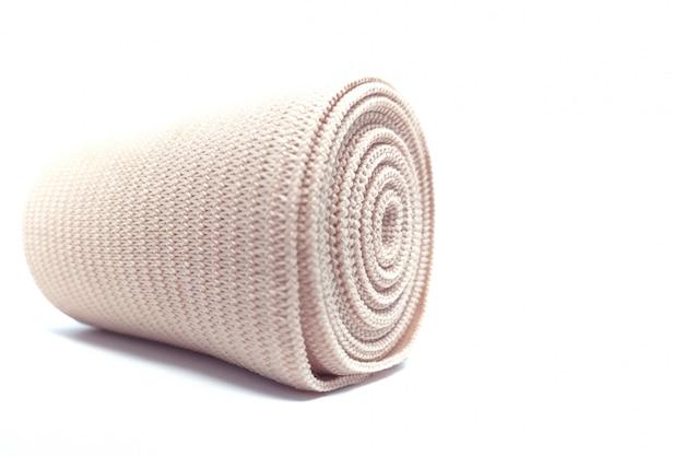 Medizinische elastische verbandrolle für die erste-hilfe-ausrüstung der unterstützung lokalisiert auf weiß.