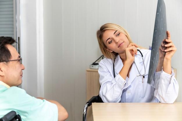 Medizinische fachleute kaukasische frau, die röntgenbild und gespräch mit asien-patient des älteren mannes hält.