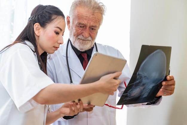 Medizinische fachleute kaukasischer älterer mann, der röntgenbild und gespräch über patient mit junger ärztin hält.