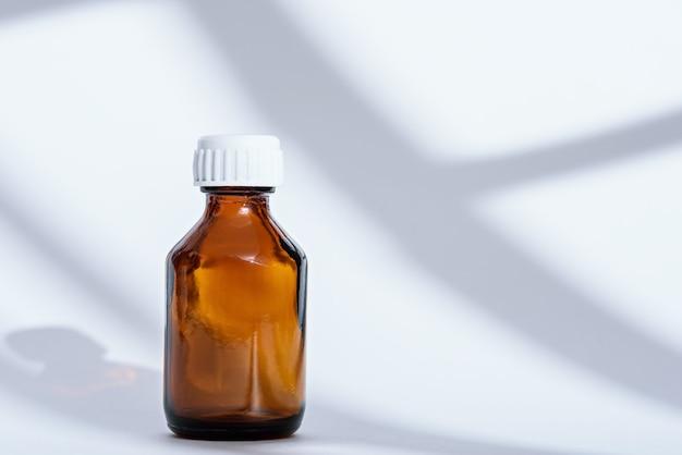 Medizinische flasche des leeren braunen glases auf weißem hintergrund mit kopienraum