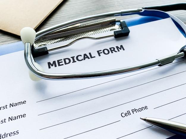 Medizinische form mit patientendaten bezüglich des schreibtisches des doktors