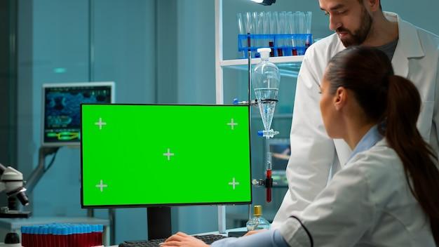Medizinische forscher, die desktop-computer mit green-screen-mock-up-vorlage im labor für angewandte wissenschaft verwenden. laboringenieure in weißen kitteln führen experimente mit chroma-key-display durch