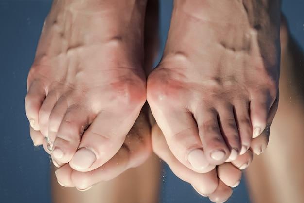 Medizinische füße mit großem knochen an den zehen und pediküre, die sich im spiegel der blauen medizin und gesundheit widerspiegeln, entspannen sich und alter und entwicklung der müdigkeit