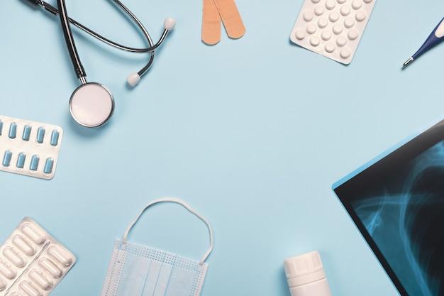 Medizinische geräte und pillen auf hellblauem schreibtisch. medizin- und gesundheitskonzept